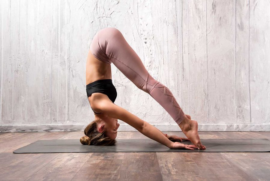 Flexible woman performing variation of sirsasana yoga pose
