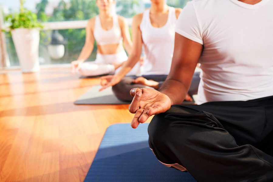 Group of meditating people, focus on instructors hand in mudra