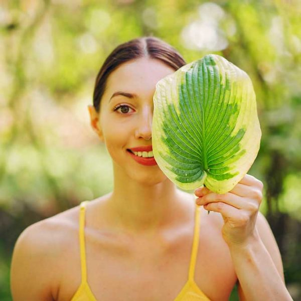Girl in a summer park. Woman in a yellow top. Lady with green leaf near face.