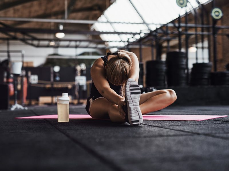 fit-young-woman-doing-stretches-on-a-gym-floor-QVWG8LX-min