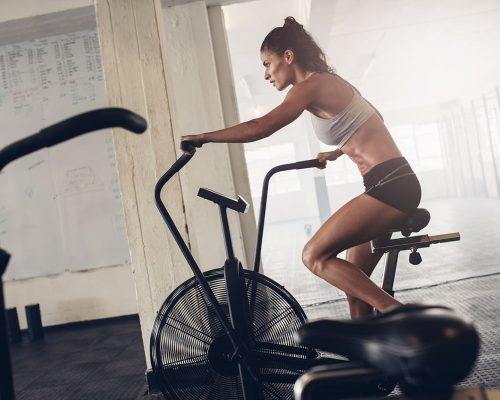 fit-young-woman-using-exercise-bike-at-the-gym-PCGRTB7-min