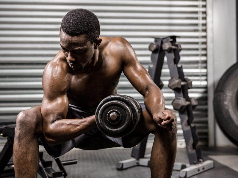 shirtless-man-lifting-dumbbell-on-bench-at-the-PQVL8YF-min