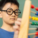 boy-learning-math-with-abacus-in-a-classroom-at-DE9N3LX-min