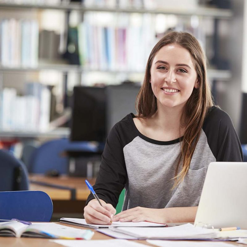 Portrait Of Female Student Working At Laptop In College Library