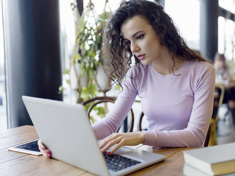 Young attractive woman working on laptop in coffee shop